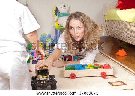 Young mother is playing with her little son - stock photo