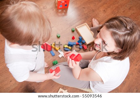 Young mother is playing with her little son. High view - stock photo