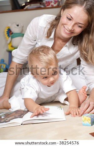 Young mother is reading book with her son - stock photo