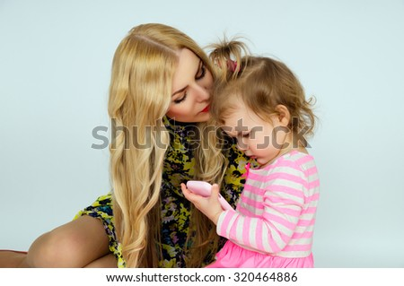 Young mother kissing daughter - stock photo