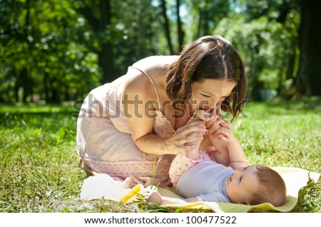 Young mother kissing feet of her baby lying on back - sunny summer day - stock photo