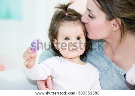 Young mother kissing her baby little girl.Shallow doff - stock photo