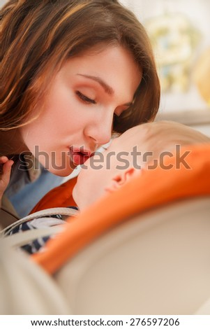 young mother kissing her baby with love - stock photo