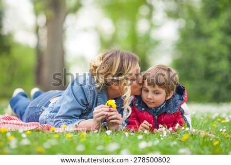 Young mother kissing her cute little son while having a picnic in nature