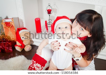 young mother kissing her little son, the boy is in Santa's cap - stock photo