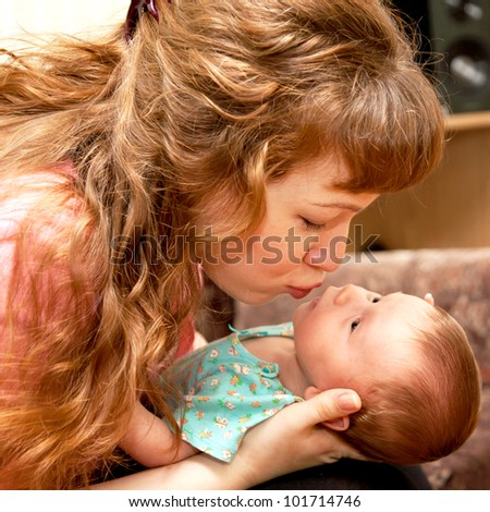 Young mother kissing newborn baby - stock photo
