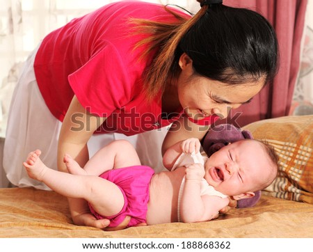 Young Mother Looking After Her Crying Newborn Baby - stock photo
