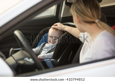 Young mother looking at baby boy sitting in car in baby seat - stock photo
