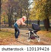 Young mother looking at her child in a baby stroller - stock photo