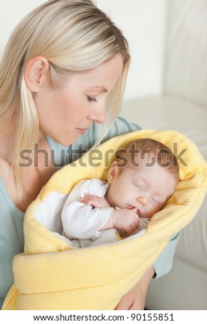 Young mother looking at her cute baby in her arms - stock photo