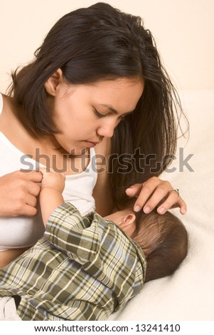 Young mother lying in bed and breast feeding infant, holding his hand - stock photo