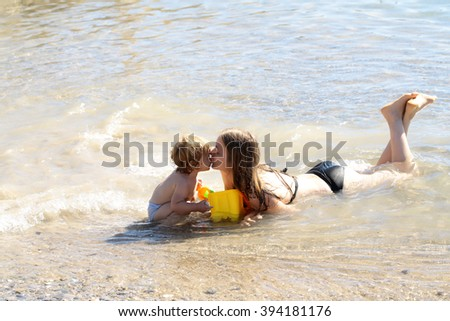 Young mother lying in sea beach wavy water kissing and playing with small cute child boy with plastic toy pail yellow color sunny day outdoor on natural background, horizontal picture - stock photo