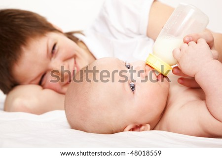 young mother lying on bed with her baby and feeding him with a bottle