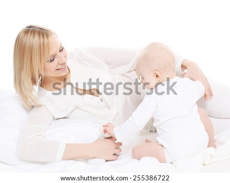 Young mother lying with her baby and playing - stock photo