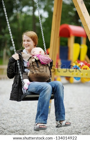 Young mother on a swing with baby in a babycarrier - stock photo