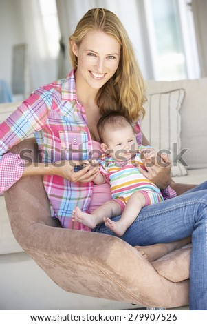 Young Mother On Sofa At Home - stock photo