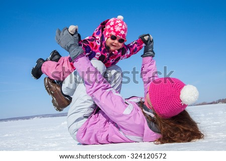 young mother playing toddler meters in the snow in the winter - stock photo