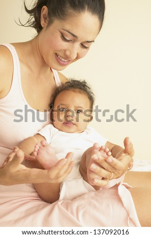 Young mother playing with baby's feet - stock photo