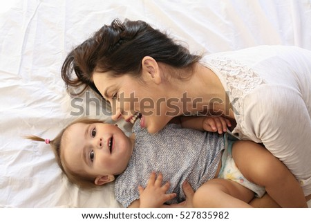 Young mother playing with her baby girl playing in bed.