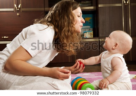 Young mother playing with her little baby daughter - stock photo