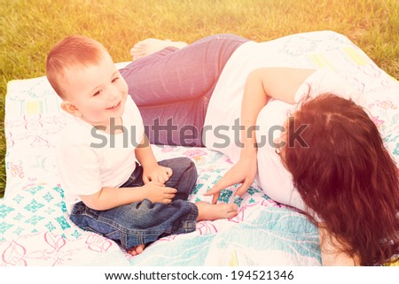 Young mother playing with her toddler son in the park.