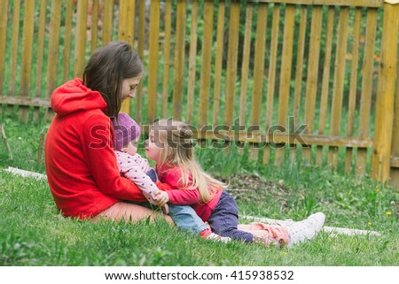 Young mother playing with kids outdoors during the spring, happy familly moments - stock photo