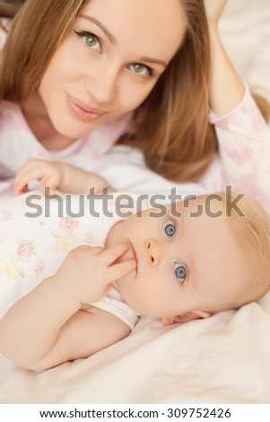 Young mother playing with little baby - stock photo