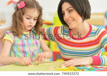young mother playing with little daughter