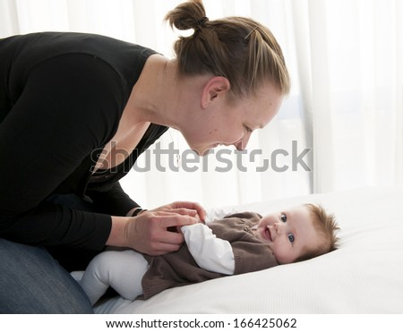 Young mother playing with sweet baby girl at home