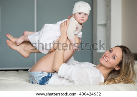 Young mother plays with the daughter in a bedroom - stock photo
