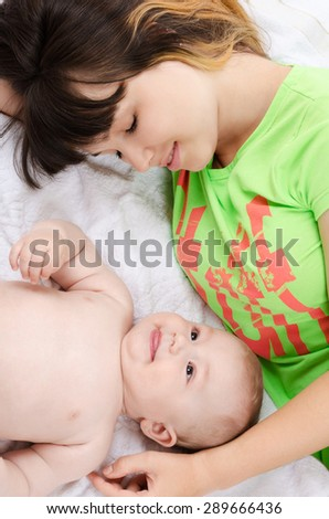 Young mother puts her baby to sleep - stock photo