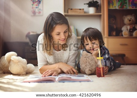 Young mother, read a book to her tho children, boys, in the living room - stock photo