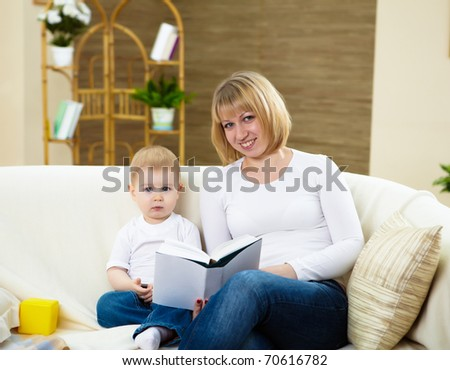 young mother reading a book to her little son at home