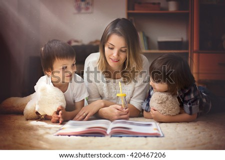 Young mother reads a book to her tho children, boys, in the living room - stock photo