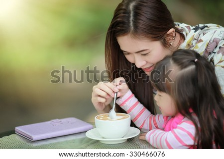 Young mother relaxing together with her little child  girl in summer outdoors