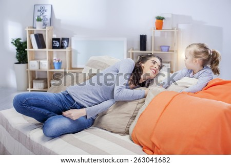Young mother relaxing with daughter in the living room, shallow depth of field