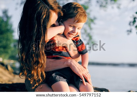 Young mother resting with his young son in the summer at sunset on the lake under a tree and hugs him. The child laughs and happy