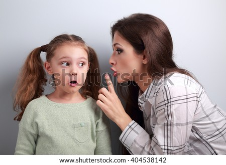 Young mother showing the finger the silence sign to her surprising funny daughter on blue background - stock photo