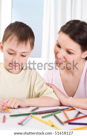 young mother sitting and draws with his son