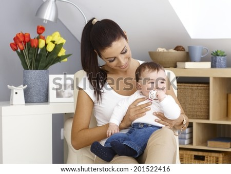 Young mother sitting in armchair at home, holding little boy in arms, smiling. Teat in mouth. - stock photo