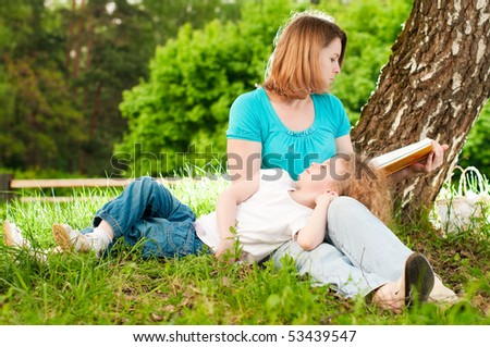 young mother sitting in grass under tree and reading book to her small daughter who is lying on knees of her mother and sleeping - stock photo