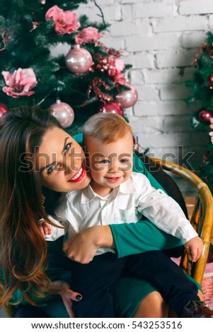 Young mother smiling and  playing with her cute  baby boy dressed in a suit. Christmas decorations. New Year eve. Winter holidays
