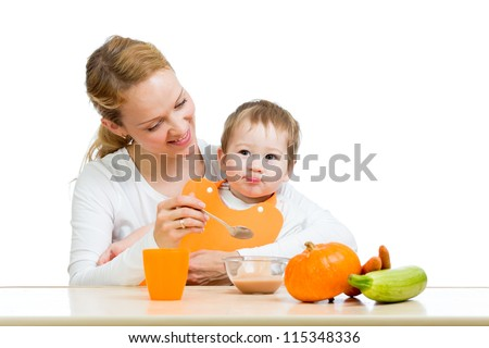 young mother spoon feeding her baby boy isolated on white - stock photo