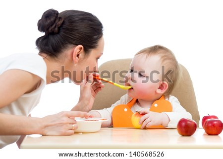 young mother spoon feeding her baby girl - stock photo