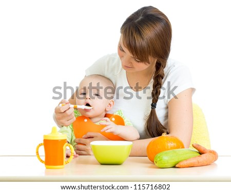 young mother spoon feeding her baby isolated on white - stock photo