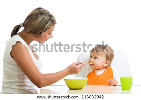 young mother spoon feeding her cute baby girl isolated on white - stock photo