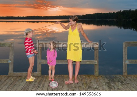 Young mother standing with her children on a wooden pier at a lake in Smaland, Sweden, in the light of an amazing sunset and kidding with her little son and catch him with a landing net. - stock photo