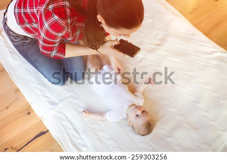 Young mother taking a picture of her cute little baby girl lying on a blanket in a living room.