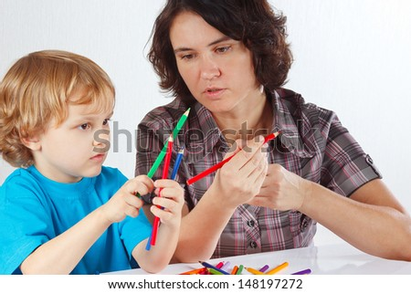 Young mother teaches her son to draw with pencils on a white background - stock photo