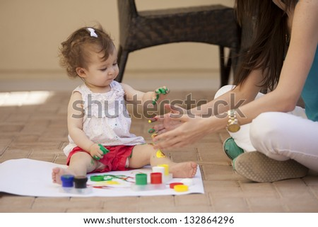Young mother teaching her baby girl how to paint